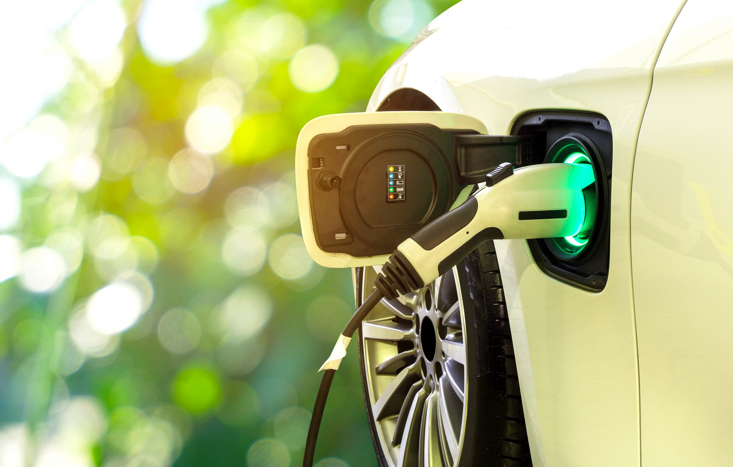 EV Car or Electric car at charging station with the power cable supply plugged in on blurred nature with soft light background.