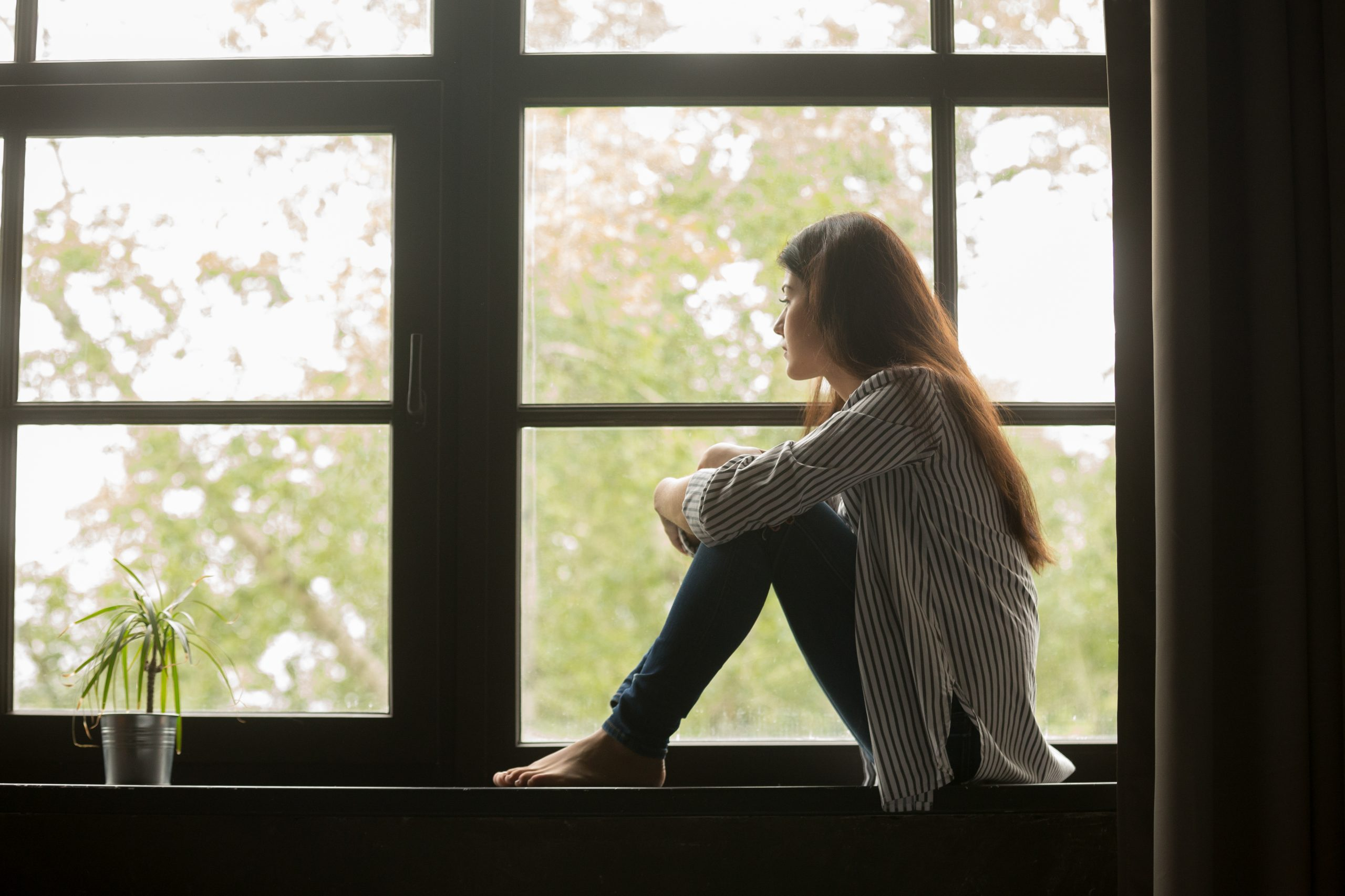Girl sitting on sill looking out window.